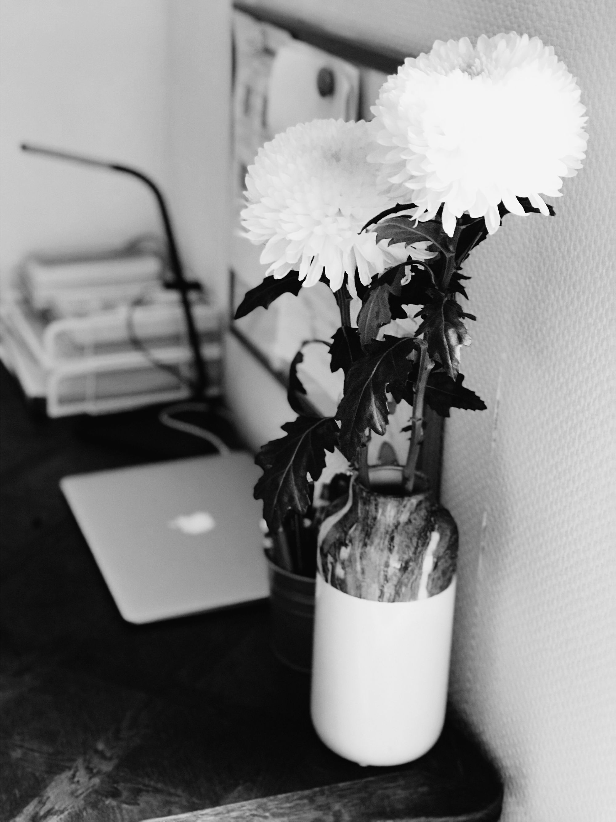 A table with some flowers and a MacBook.